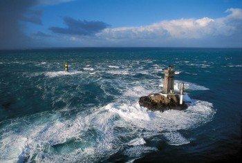 Der rauhe Atlantik umspült den Leuchtturm vor der Pointe du Raz.