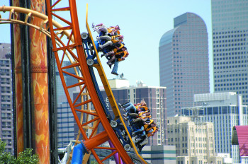 The half pipe roller coaster at Elitch's with the Denver skyline in the background.