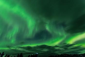 Mit bloßem Auge betrachtet zeigen sich Nordlichter meist als weiß-leuchtende Schlieren am Himmel. Durch die richtigen Kamera-Einstellungen entstehen die typisch grünlichen Aufnahmen.