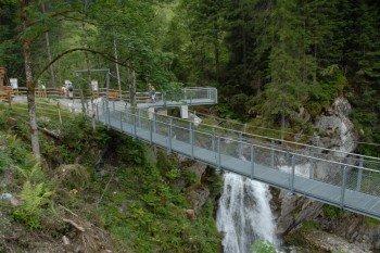 Eine Hängebrücke führt über den Wasserfall im Unteren Grund