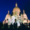 Die Basilika Sacré-Coeur wird bei Dunkelheit beleuchtet.