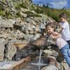Kinder spielen am Wasserlauf.