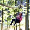An einem Rollschlitten hängend fliegst du mit der Fly-Line durch den Wald.