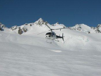Auf dem Gletscher landender Helikopter