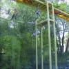 Im Hochseilgarten klettern Besucher auf Stahlgerüsten über dem Wasser.