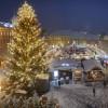 Blick vom Rathaus auf die verschneiten Buden des Klagenfurter Weihnachtsmarktes. Die große Tanne ist mit Lichterketten und Christbaumkugeln geschmückt.