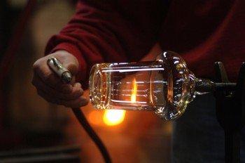 Ein Glasarbeiter beim Abühlen der Glasmasse