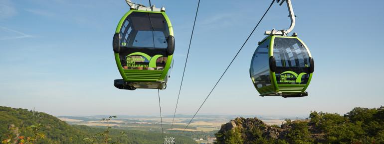 Grüne Kabinen mit Glasfußboden schweben über das Bodetal zum Hexentanzplatz