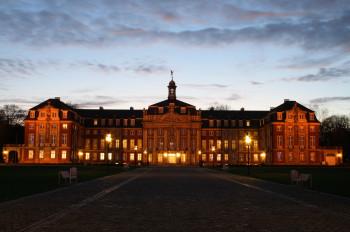 Das Schloss Münster erstrahlt in der Abenddämmerung.
