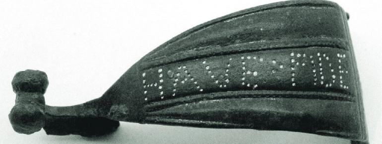Eine römische Fibel mit lateinischer Inschrift.
