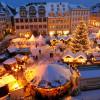 Ein großer beleuchteter Weihnachtsbaum erstrahlt in der Mitte des Weihnachtsmarktes.