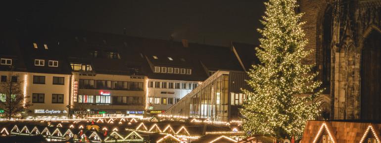 In der Mitte des Platzes befindet sich ein großer geschmückter Weihnachtsbaum.
