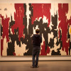 A man standing in front of a painting at the Clyfford Still Museum in Denver.