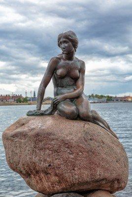 The Little Mermaid on the reddish stone at Copenhagen's port entrance