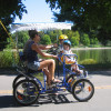 Family rides in a bicycle cart at Washington Park.