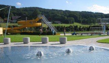 Das Kinderbecken (im Vordergrund) und die große Wasserrutsche (im Hintergrund) im Freibad Thalgau.