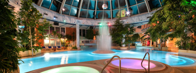 Die Whirlpools und das Erlebnisbecken unter der großen Glaskuppel der Therme