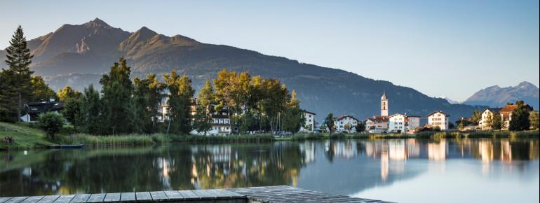 Der Laaxersee liegt vor einem tollen Bergpanorama im Schweizer Kanton Graubünden.