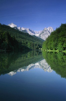 The mountain-scape is reflected by the clear lake water.